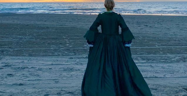 Gwynne Phillips in The Templeton Philharmonic's short film PORTRAIT OF A WOMAN WITH FLAMES. She stands on a beach at sunrise, in a green 18th century dress. Her back is to camera.