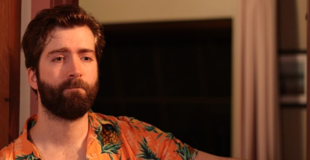 Stephen stands in a doorway wearing a Hawaiin shirt. He looks down past the camera reminiscing about the one that got away.