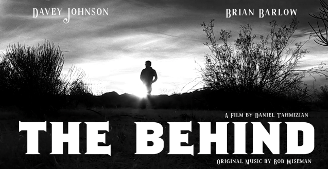 In grainy black and white a man walks the desert silhouetted against the sun. He is moving forward but looking back, desert shrubs in the foreground. The film is called The Behind. It stars Davey Johnson and Brian Barlow. A film by Daniel Tahmizian with original music by Bob Wiseman.