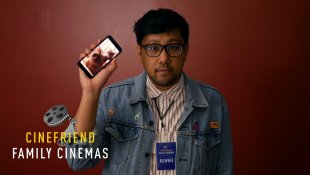 """We see Ronald from the waist up in this mock movie theatre pre-show commercial. He wears glasses, a jean jacket and a movie theatre lanyard, while holding up a cell phone with the screen showing his cat screen saver. In the corner is a logo that reads """"Cinefriend Family Cinemas."""""""