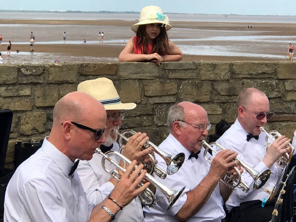 Cleethorpes band enetertaining a young listener on Cleethorpes sea front