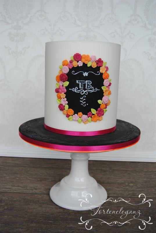 weisse Torte mit schwarzem Logo und Blumen Titel
