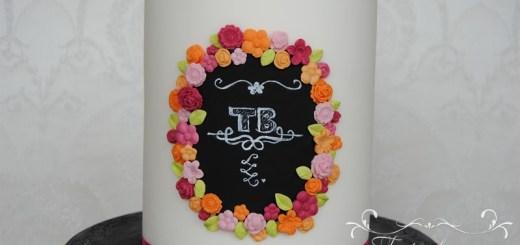 weisse Torte mit schwarzem Logo und Blumen