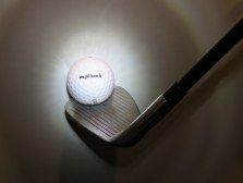 a golf ball and iron