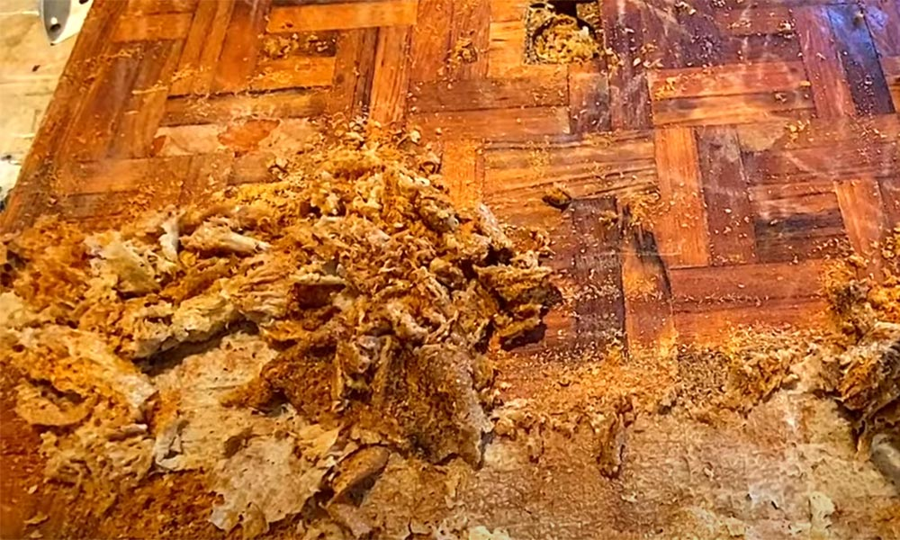 Pile of dried varnish removed with TotalBoat TotalStrip and a scraper