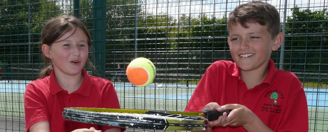 Children having a great time learning tennis