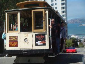 Cable Car auf einem Hügel in San Francisco und im Hintergrund die Bucht mit Alcatraz