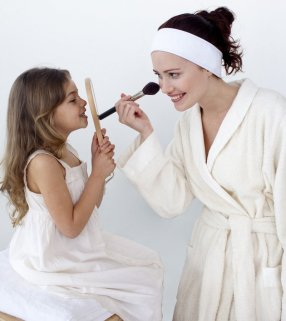 Mother applying blusher with her daughter