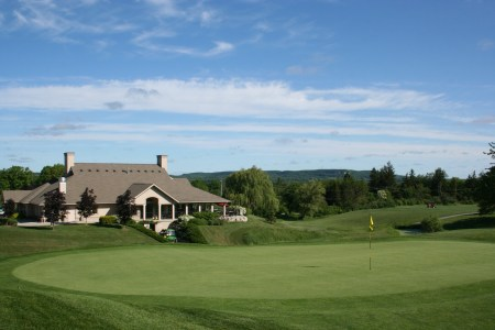 Lowville golf course clubhouse in spring with green and escarpment in background