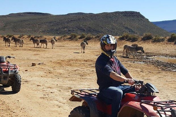 ATV rider with zebra in background