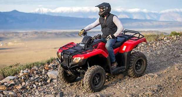 ATV rider on dirt road looking at view