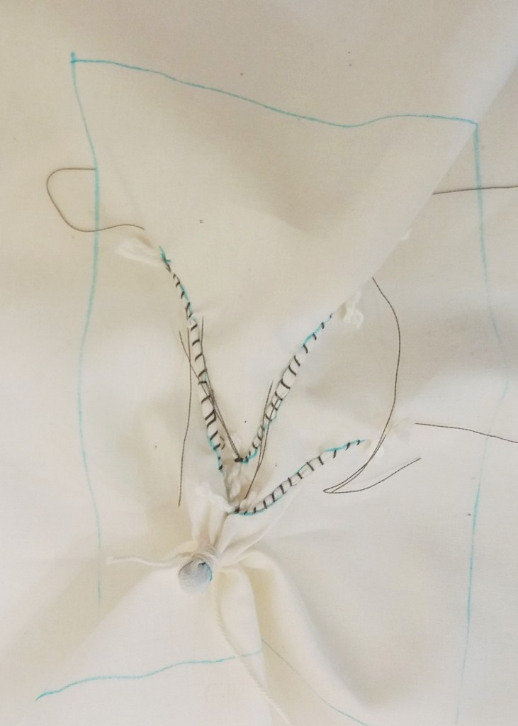 Plain undyed fabric showing guntai stitch plus a bead tied in