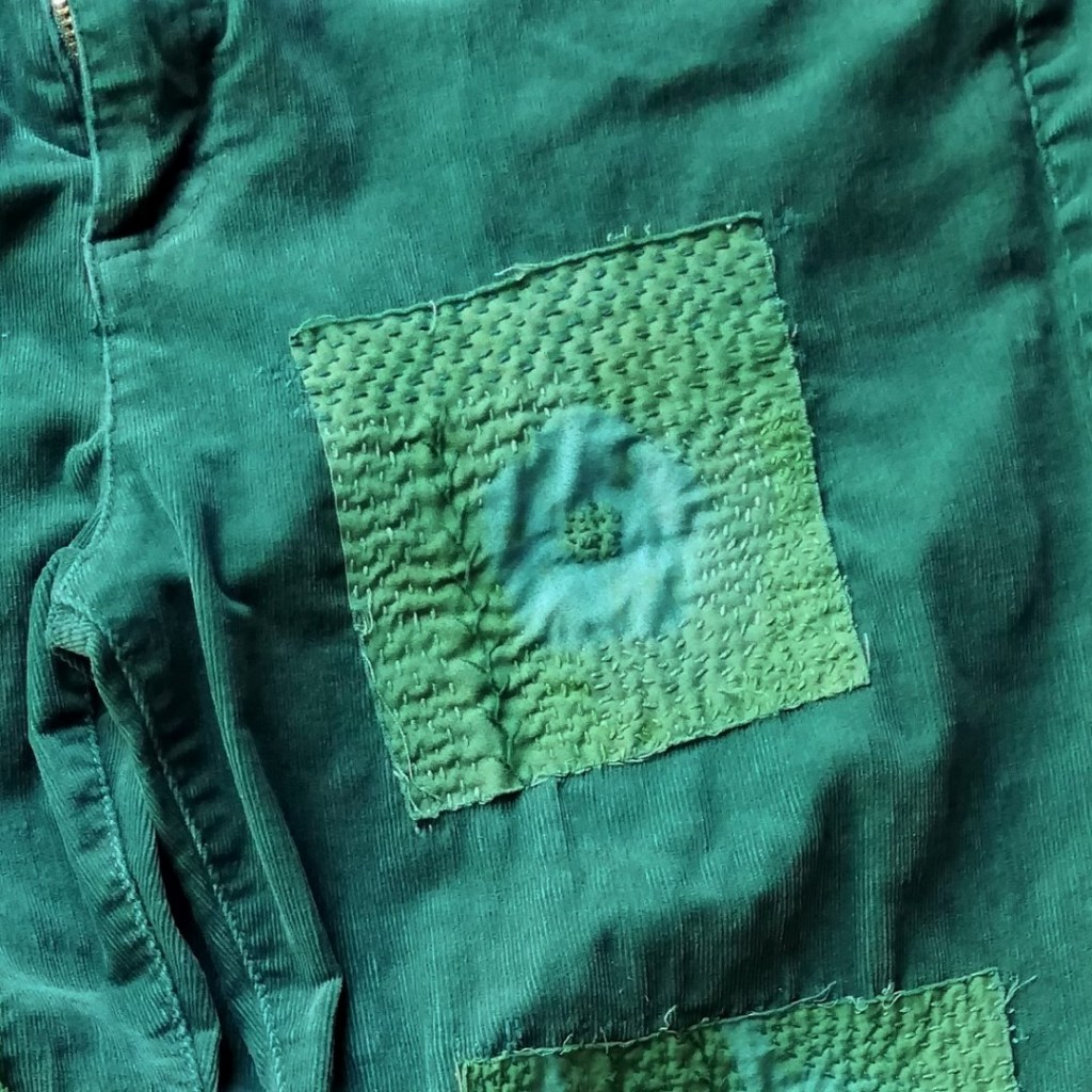 shows a hand embroidered green patch of shibori fabric