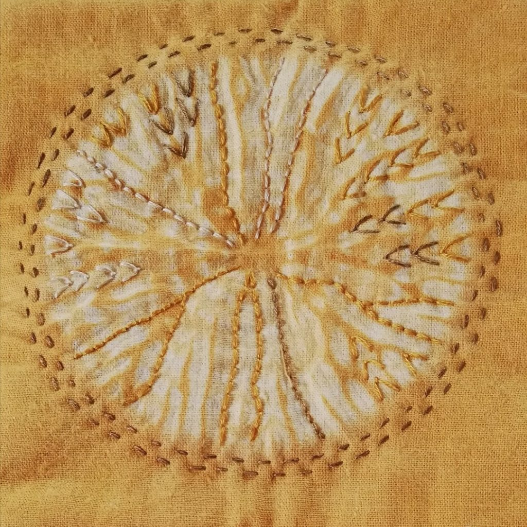 Gold fabric with circular design and embroidery