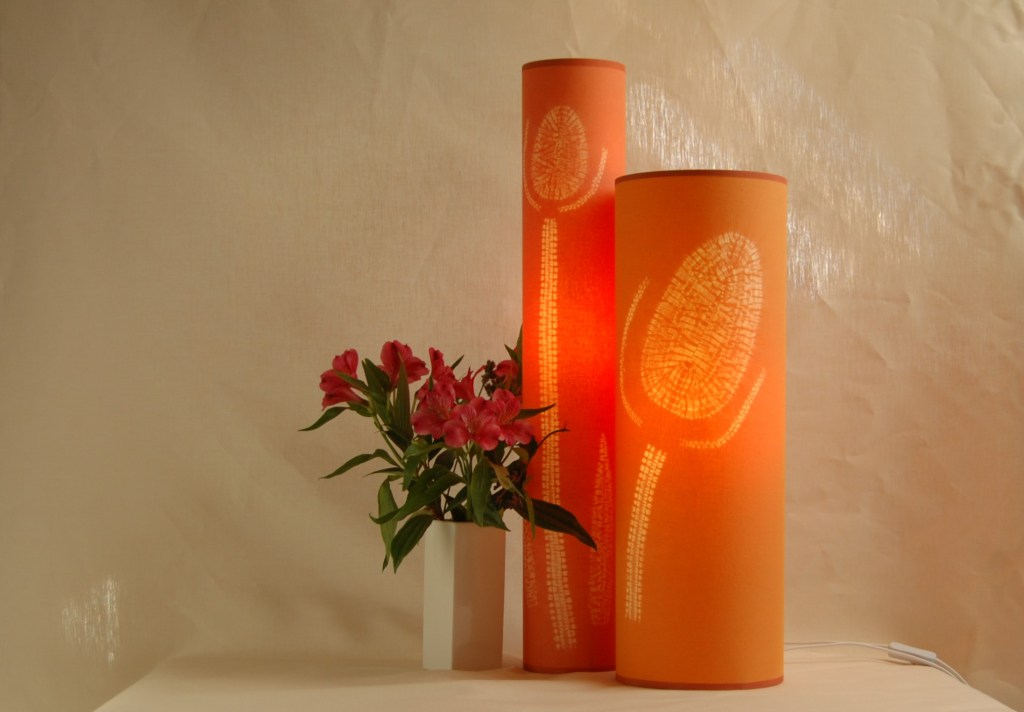 two free standing ornage lamps with teasel designs on