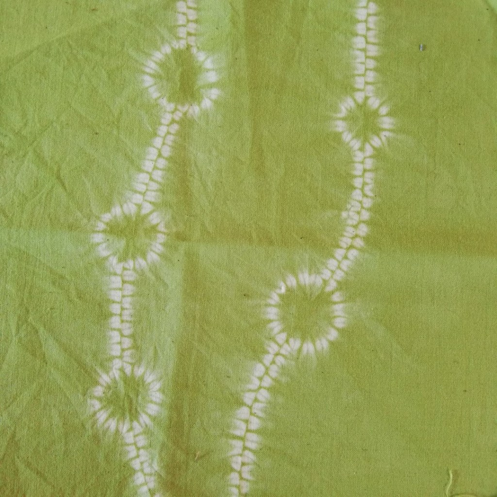 shows white seaweed pattern on a green fabric