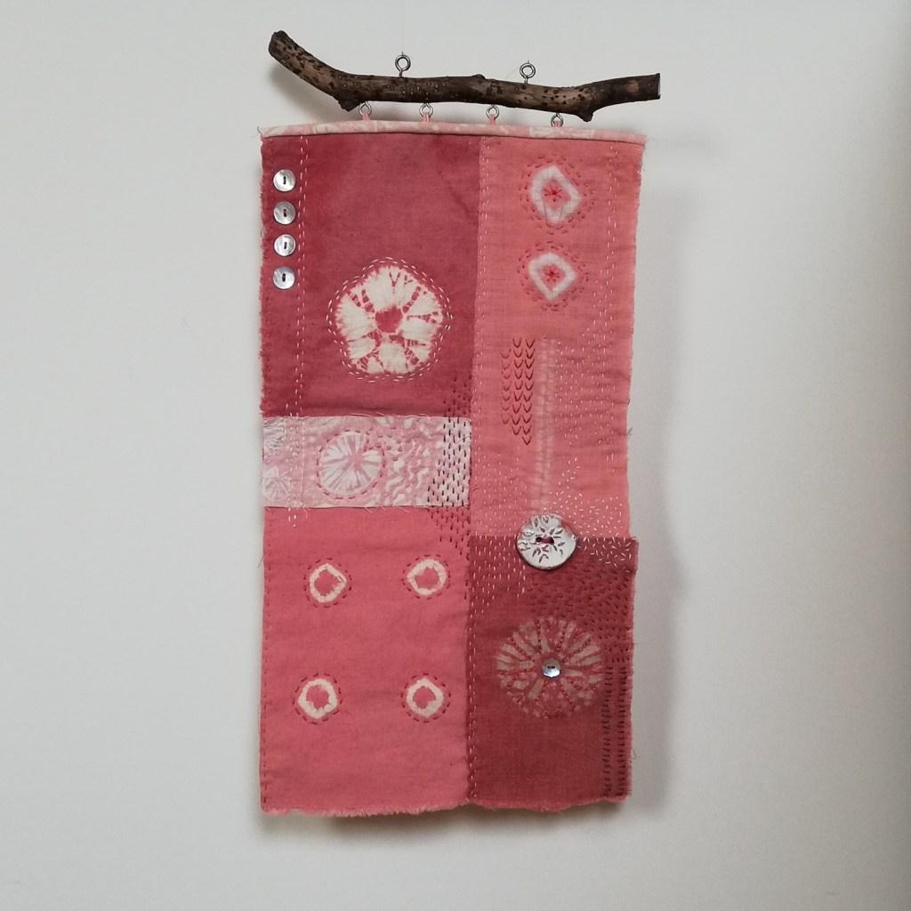 Madder dyed small shibori hanging on a white wall