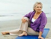 Elderly woman doing yoga on beach. - Copyright – Stock Photo / Register Mark