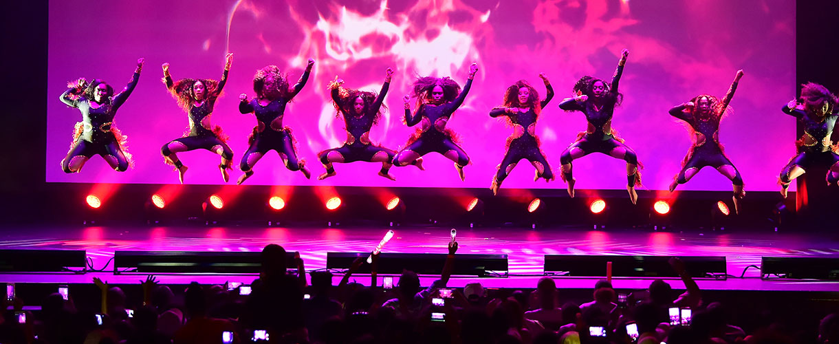 nine dancers jumping with hands up in air