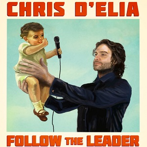 Chris D'Elia holding baby with microphone