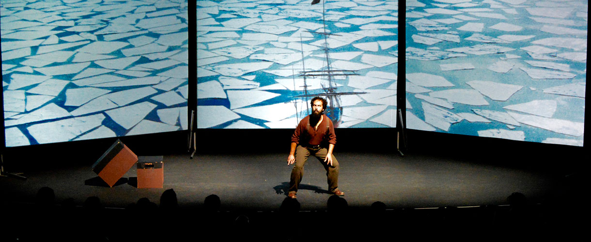 Man on stage in front of ice images