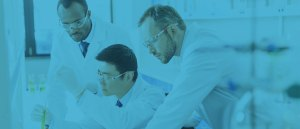 Photo of a team of pharmaceutical professionals leaning in a lab doing testing