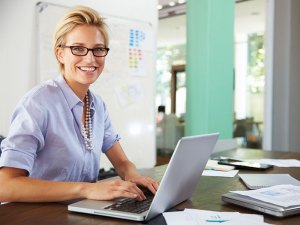 A picture of a female employee smiling at her desk.