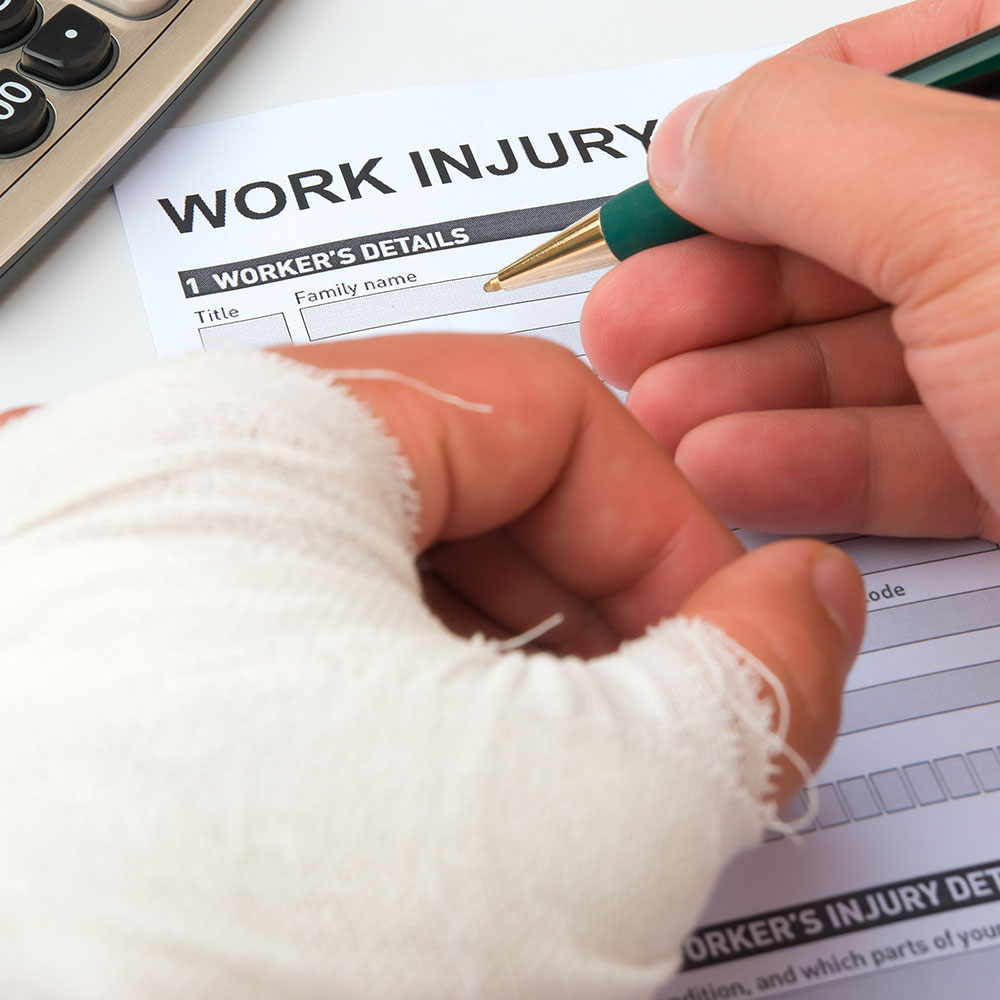 Picture of an injured person filling out a workers' compensation form.