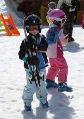 5 year old carrying his skis