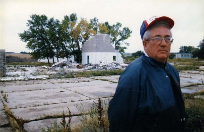 1997, Alvin Meitheral (ret. Master Warrant Officer, Construction Engineer) stands before the rubble of the firehall. Headquarter building appears in the right background.