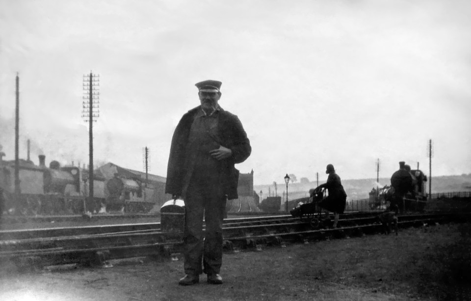 """Driver Ernie Parr, a distant relative, showed Peter round the sheds at Grantham when he was a schoolboy and he had already set his mind on getting a job at the Loco. Behind Ernie is the ramp leading to the coal stage. There is no sign of the coaling plant, so the photograph must date from before 1937. On the right a woman is crossing the tracks with a child in a push chair. Peter thinks she will be going to the office to collect wages due to her husband (or perhaps a brother or her father). Close examination shows that the child is holding onto a shopping basket and they are being followed by a dog! Ernie retired on the same day that Peter started working at the Loco. He is carrying a metal toolbox. """"All the drivers had them,"""" Peter told me. Photograph lent by Peter Wilkinson."""