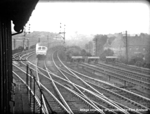 Viewed along the eastern side of the box in 1937, the junction for Nottingham is in the foreground. Leading in from lower right are connections from the Up Bay platform, loading dock and sidings. On the extreme left is a connection from the Down Nottingham line to the Up Nottingham line, which enabled locos off the shed to access the Up Main line through the station to Grantham Yard box, for locomotive changes on southbound trains. The Coronation service recedes at speed on the Main line towards Barrowby Road, its unique Observation Car bringing up the rear. Taken from a cine film shot by photographer and film maker Walter Lee of Grantham. © Lincolnshire Film Archive