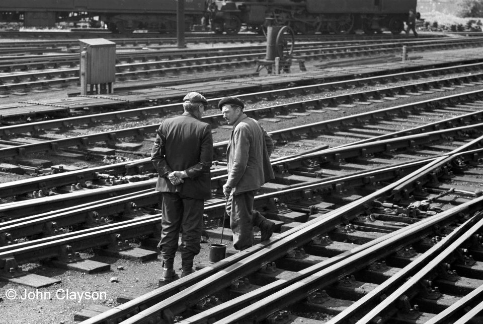The man on the right is Augustus (Gus) Summers, a former German PoW who worked for Tearson's (Terson's?), a contractor who carried out track maintenance and repairs. With his pot of oil and long-sticked brush he is lubricating the point mechanisms near the north end of the station. If you look at the track in the foreground you can see that there is fresh oil around the special rail chairs fixed to the crossing timbers, known as 'slide chairs', on which the switch blades slide. The man on the left is Tom Plummer, the North End Ganger at Grantham, who is acting as 'Look-Out' – he is carrying a set of flags under his left arm, on which he also has strapped an enamelled 'Look-Out' armband. This was, and still is, a vital role - keeping watch for, and giving warning of, approaching trains which might not be noticed by track workers engaged in a maintenance task on lines which remain open to traffic. The regular lubrication of points is important because the lengths of rail which move across the slide chairs when points are changed are heavy – on a crossover (two points worked together) they might weigh more than a tonne. The signalman's muscle power also has to move the heavy point rods linking the signal box lever frame with the points. Today, most points on main lines are worked by electric motor. The object in the centre background is a drilling machine, which was used for boring holes in point stretcher bars. May 24th 1962 Photograph by Cedric A. Clayson,