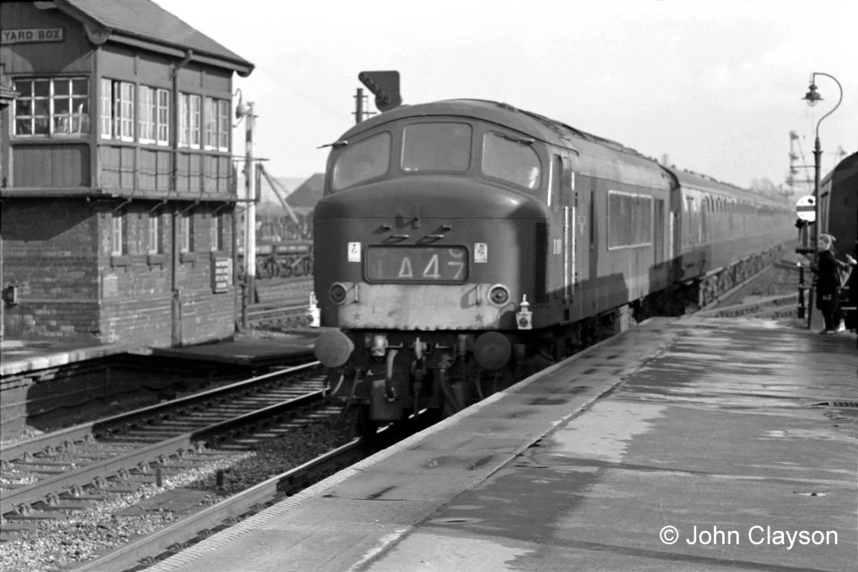 On April 18th 1963 a northbound passenger train passes the Yard Box on the Down Main line, hauled by a diesel electric locomotive of the 'Peak' class, so called because the first ten were named after English and Welsh mountains. Train 1A47 would be the southbound The Heart of Midlothian at that time, so it would seem that this locomotive has faulty train indicator blinds. It is also carrying 'Class 1' express passenger train oil headlamps, as used on steam locomotives, which may be intended to show that the indicator blinds are not to be relied upon. Peak locomotives seemed prone to this problem. This could possibly be service 1A42, the 15:00 from King's Cross to Newcastle, which would be at Grantham around 16:45. Photograph by Cedric A. Clayson,