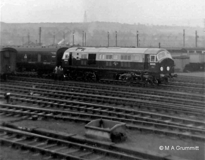 """Progressing away from the camera this view from the Yard Box shows: o the spur into the dock at the end of the Down platform o the Down Slow line (partly obscured by the concrete bunker) o the north end of carriage sidings 2, 3, 4 and 5 (some stored roling stock being visible on the left) o the Up and Down Goods line (not signalled by the Yard Box), on which the train is standing. The locomotive is brand new Type 2 diesel electric No. D6122 on a trial run from Doncaster to Grantham. Mick Gummitt tells us """"It had just run round its train of empty stock ready to go back to Doncaster - hence all the attention by the inspectors."""" These locomotives didn't normally operate in the Grantham area. D6122 went into service at Ipswich in the second half of 1959, soon after this trial trip. They were not the most reliable machines. All 38 initially sent south (to Hornsey, Stratford and Ipswich) returned to Scotland during 1960 to see out their relatively short service lives. Photograph by Mick Grummitt."""
