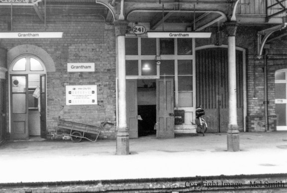 "The end of the Book Stall is just in view on the left. The open doors (centre) were to the ""Postal Authorities Room"" The larger double doors behind the bicycle was the Luggage Entrance"" The doors just coming into view on the right lead through to ""Enquiries"" with another room behind this for use by ""Station Masters Clerks"" Copyright Image - Mel Smith"