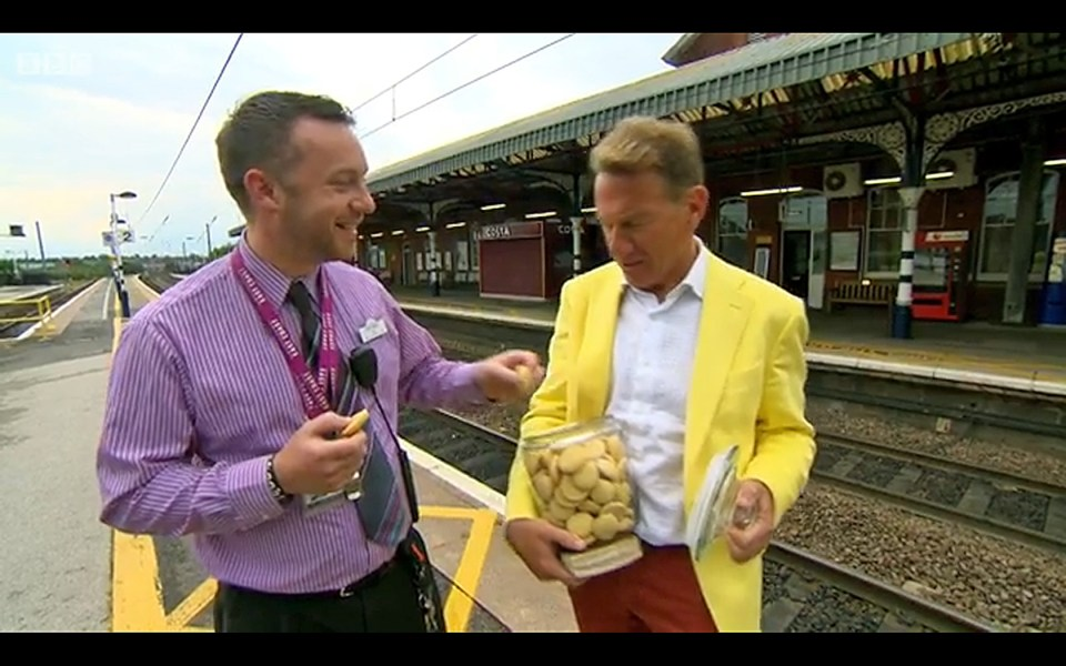 Michael Portillo shares his Grantham Gingerbread with a member of the East Coast staff at the station. From Great British Railway Journeys Series 6: 11 Derby to Grantham, © BBC