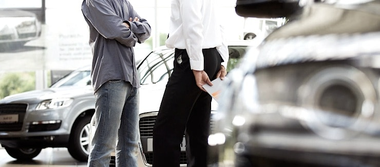 A young man talking to a car salesman