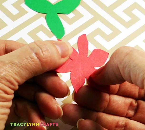 To create a more attractive design, curl the red and green leaves of the poinsettia cut outs. You can do this by scratching with your fingernail.