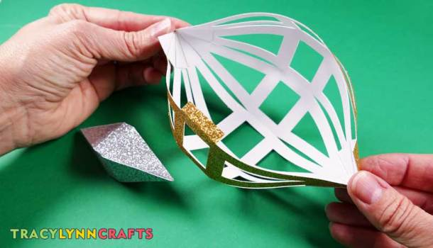 Push the ends of the gold ornament to open it up to add the silver ornament before gluing the last tabs on the gold ornament