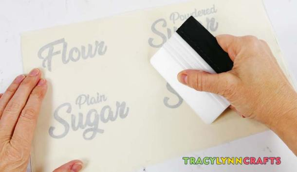 Use a burnishing tool to secure the vinyl pieces of the kitchen canister labels to the transfer tape