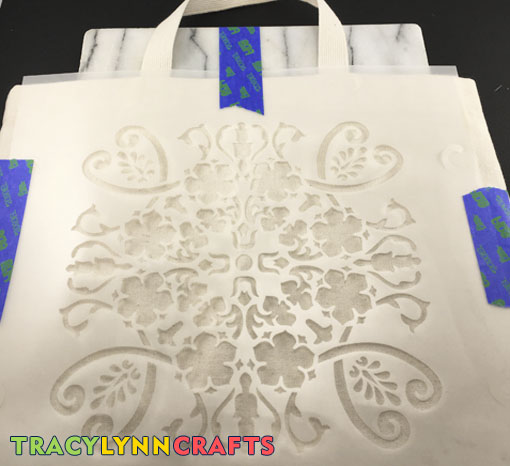 DIY Stenciled Tote Bag - Secure the stencil to the tote bag with tape