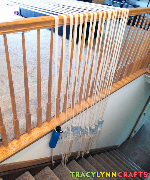 Before my warping trapeze - weighting the warp with water bottles over the banister
