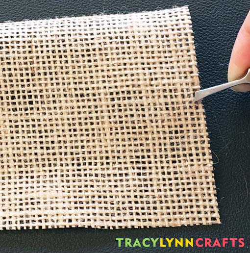 Use tweezers to grab an end of the burlap to help pull it out of the cloth