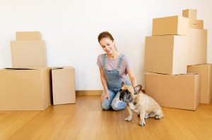 happy-woman-with-dog-and-boxes-moving-to-new-home-PRLJ6R2