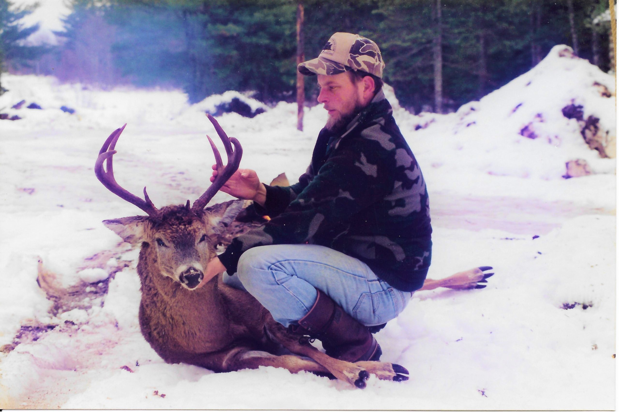 photo of a hunter with deer in the snow