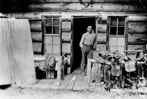 A man leaning against the doorframe of a log cabin.