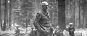 A uniformed middle-aged man standing with hands in pockets in a grove of trees