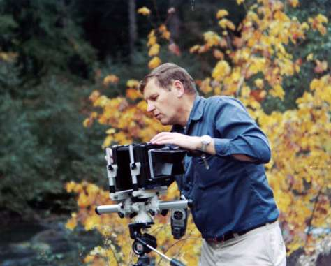 A man adjusts a large camera on a tripod with yellow fall foliage in the background.