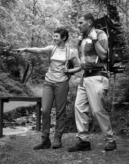 A woman and a man stand beside a bridge over a creek as the woman points to something beyond the frame of the photo.